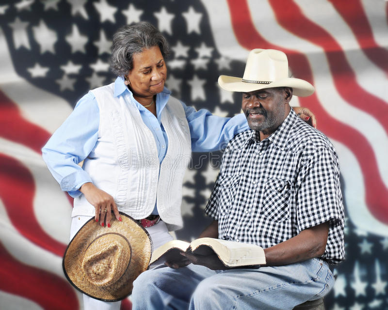 God and Country Cowboys. A mature African American cowboy couple reading the Bible with a stars and stripes background royalty free stock photo