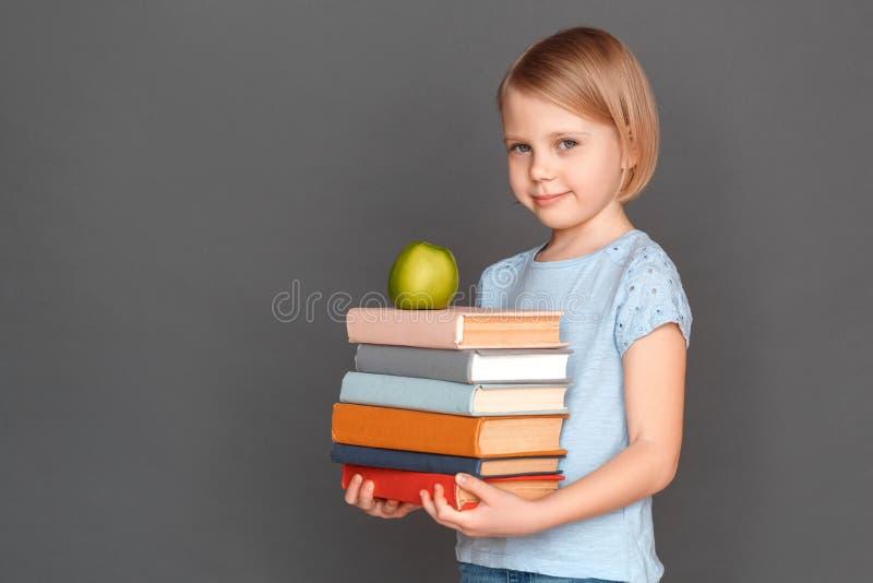 god deltagare Liten flicka som isoleras på grå färger med högen av böcker och att le för äpple som är blygsamt royaltyfri fotografi