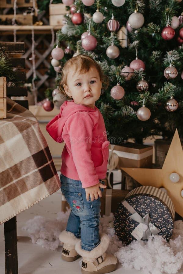 God jul och Grattis på helgdagar! Den lilla flickan i Cute dekorerar julgranen - bild royaltyfria bilder