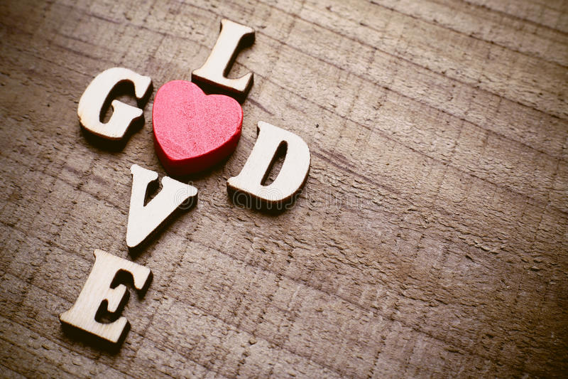 God is Love. Concept text lying on the rustic wooden background royalty free stock images
