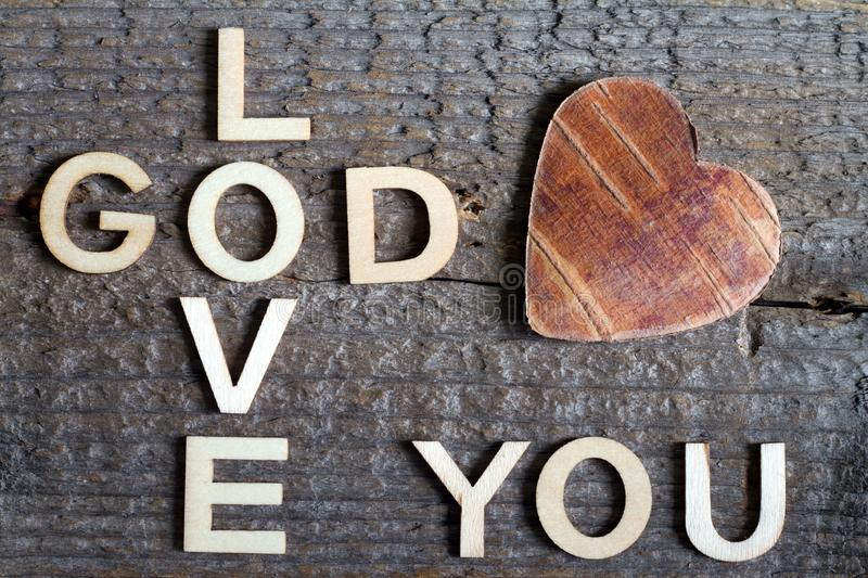 God is love letters with cross and heart religion concept on wooden background. Closeup stock photos