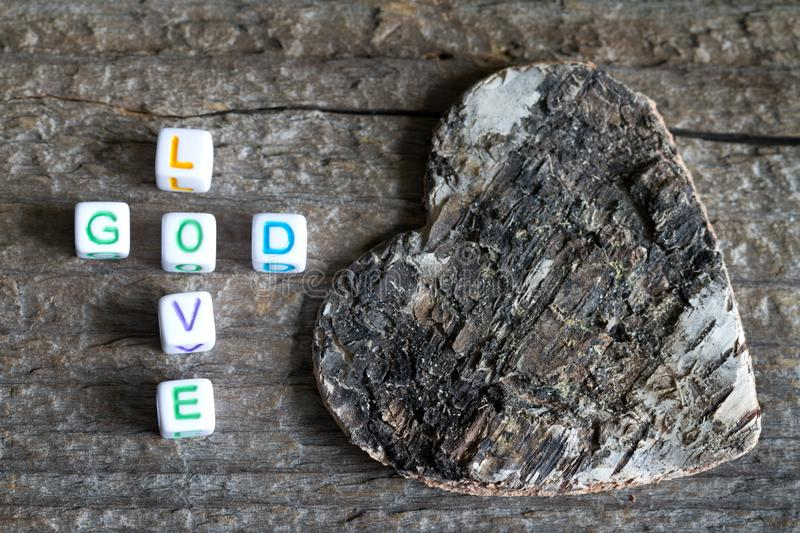 God is love letters with cross and heart religion concept on wooden background. Closeup stock photography