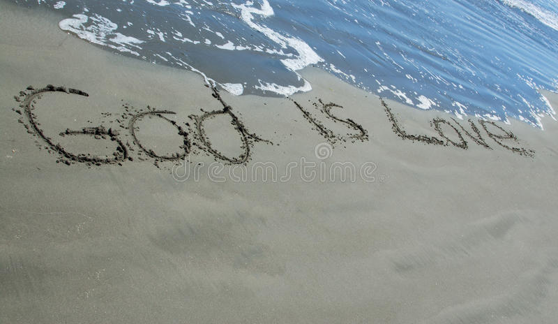 God Is Love Sand. God is Love written in sand as the waves wash close to it royalty free stock photos