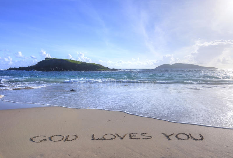 God Loves You written in sand on beach. Message in sand reads God Loves You on tropical Caribbean beach of Isla Culebra in Puerto Rico with small islands in royalty free stock images