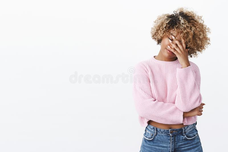 God not again. Ashamed and tired young woman with curly blond haircut making facepalm gesture holding hand on face and. Close eyes drained and fed up, exhausted royalty free stock photography