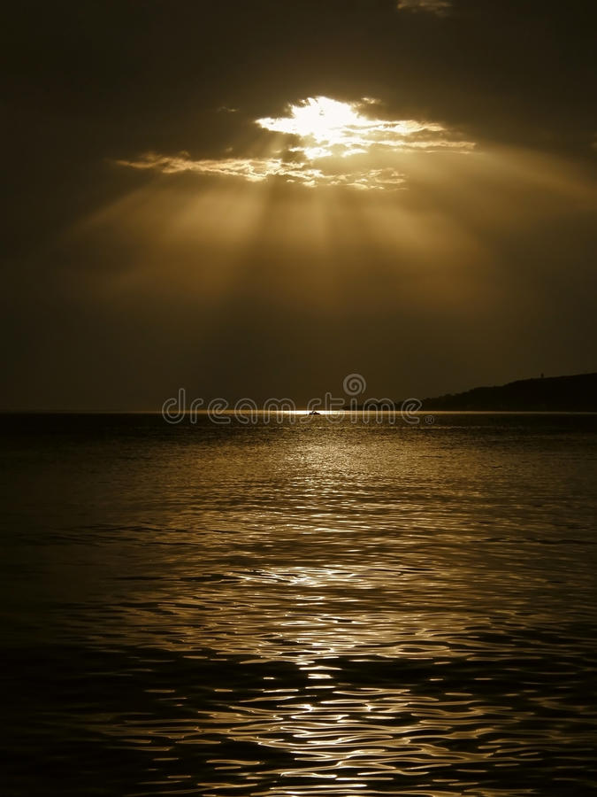God's rays and a boat on the sea royalty free stock photography