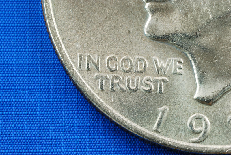 In God We Trust from the dollar coin. Isolated on blue royalty free stock photography