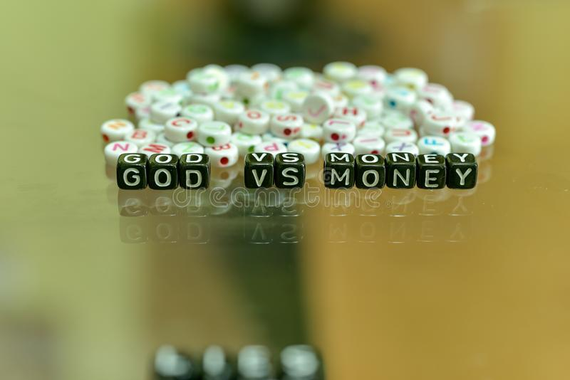 GOD VS MONEY  written with Acrylic Black cube with white Alphabet Beads on the Glass Background.  royalty free stock photography