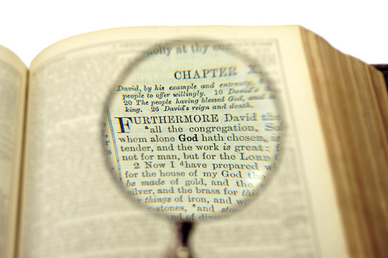 The God word comes bigger under magnifier. On a bible page stock photo