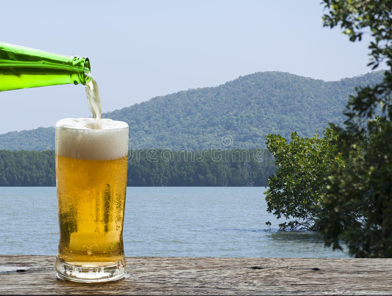 Goda della birra con il paesaggio del mare immagine stock