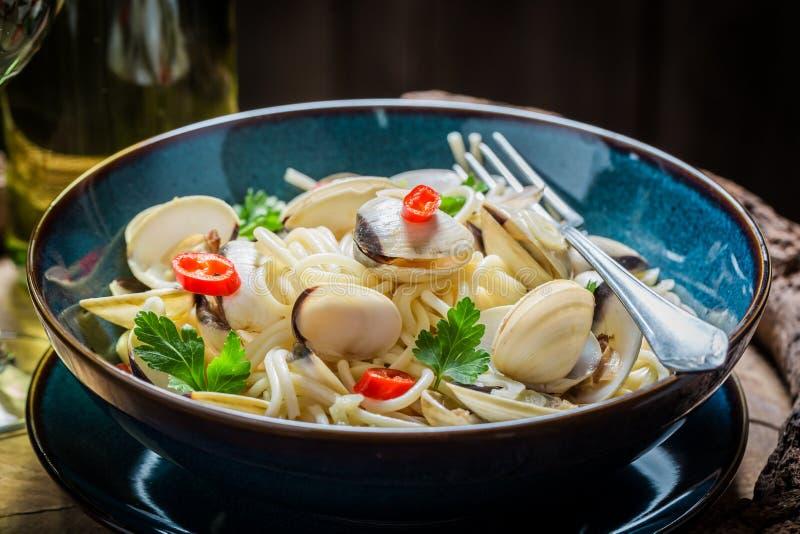 Goda della vostra pasta dei frutti di mare con le vongole, il prezzemolo ed i peperoni immagini stock
