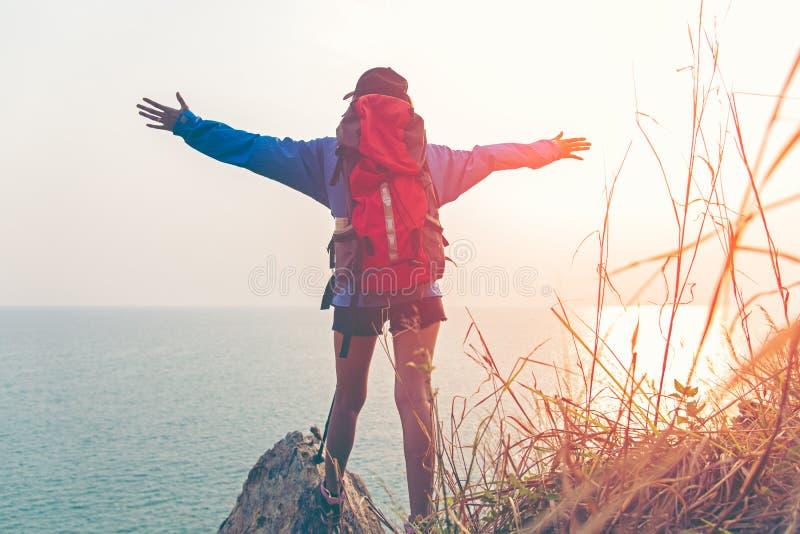 Goda för frihet för fotvandrarekvinna lycklig känslig och segerrik fasadbeklädnad för stark vikt på det naturliga berget, royaltyfria foton