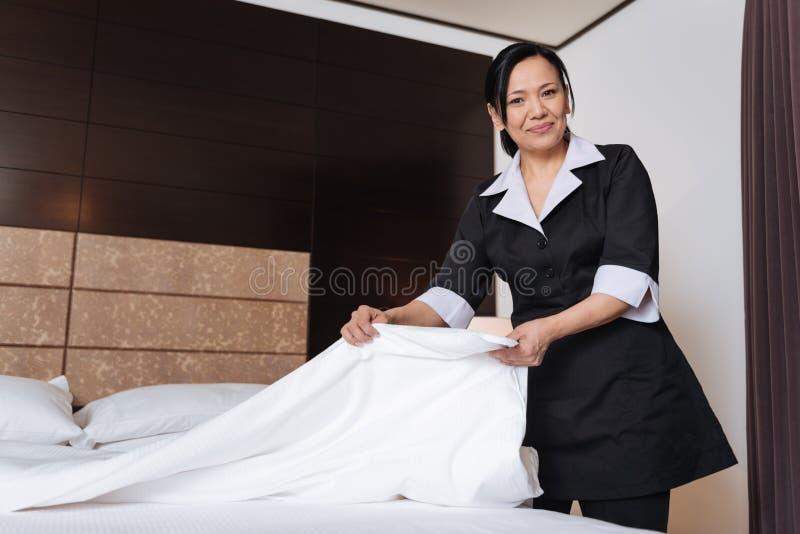 Goda som ser ändrande sängkläder för trevlig hotellhembiträde arkivbilder