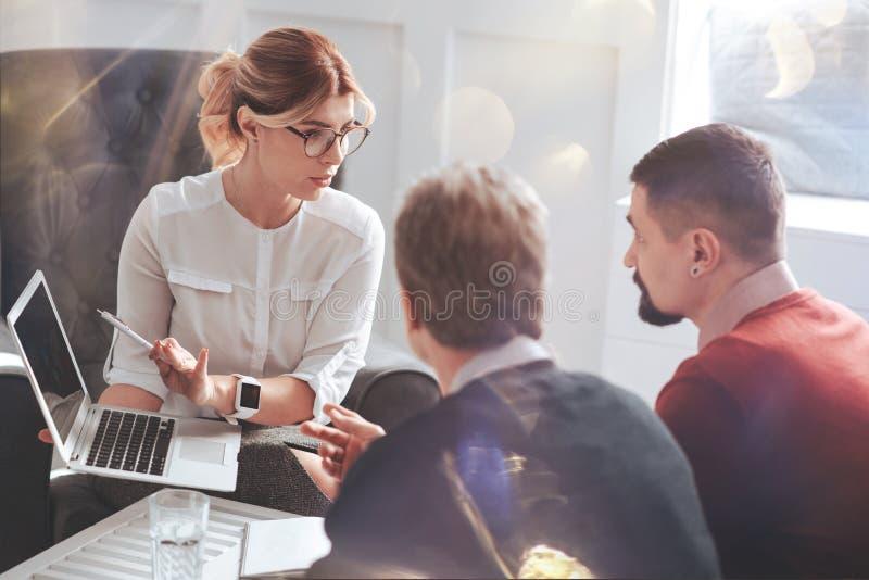 Goda som ser den attraktiva affärskvinnan som pekar på bärbar datorskärmen royaltyfri bild