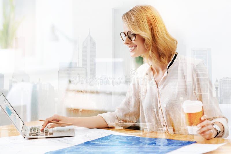 Godan som ser kvinnan som arbetar med en bärbar dator och, skissar arkivbild