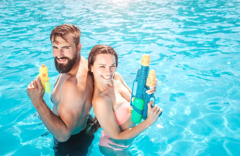 Godd男人和妇女在游泳池在照相机站立并且看 他们摆在并且微笑 人举行水枪 库存图片