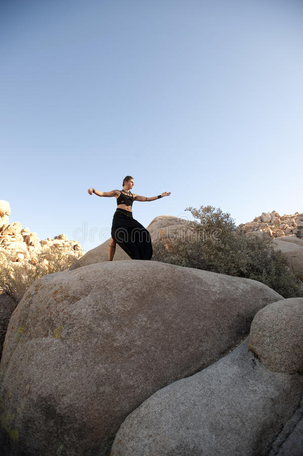 Goddess Tai Chi. Beautiful woman practicing tai chi in a fantastic feminine boulder landscape royalty free stock image