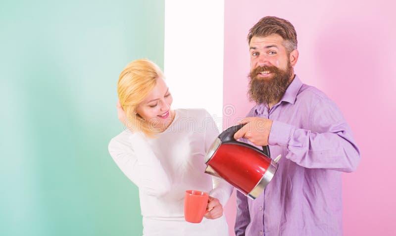 Godendo della mattina piacevole insieme Uomo con il bollitore elettrico e donna con la tazza pronta a bere il caffè di mattina Ot immagine stock