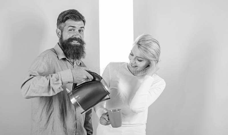 Godendo della mattina piacevole insieme Uomo con il bollitore elettrico e donna con la tazza pronta a bere il caffè di mattina Ot immagini stock libere da diritti