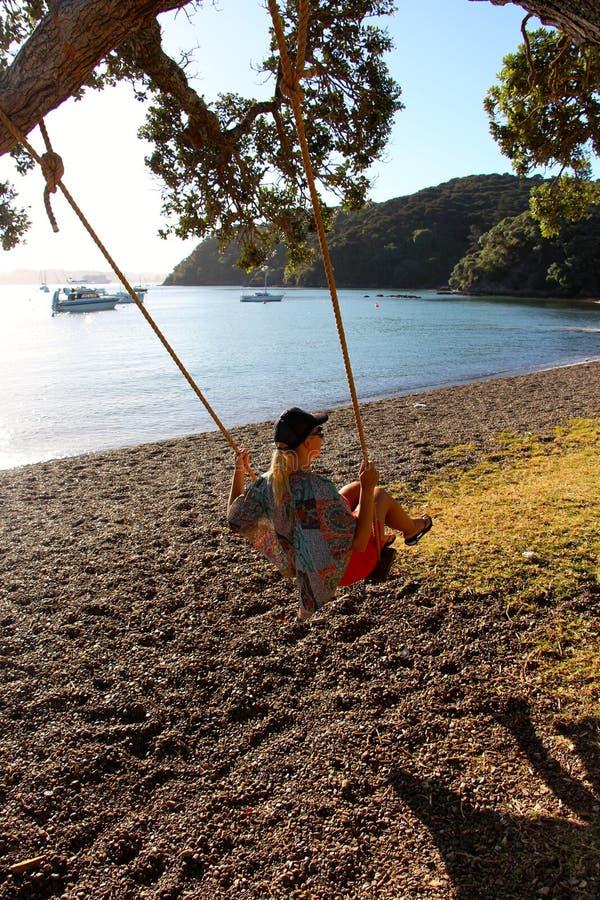 Godendo di un'oscillazione giù dalla spiaggia al tramonto fotografie stock