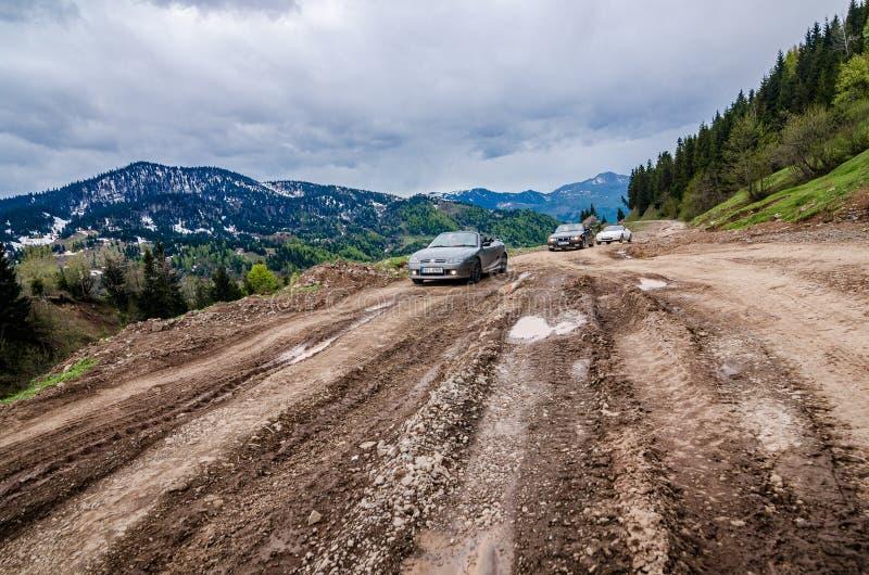 Goderdzi Gruzja, Maj, - 8, 2017 Odwracalni samochody iść na łamanej głównej drodze gruntowej w górach obrazy royalty free