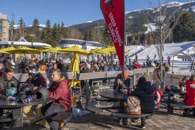 Godere dei pensionanti della neve e degli sciatori doposci alla stazione sciistica di Whistler, BC fotografia stock libera da diritti
