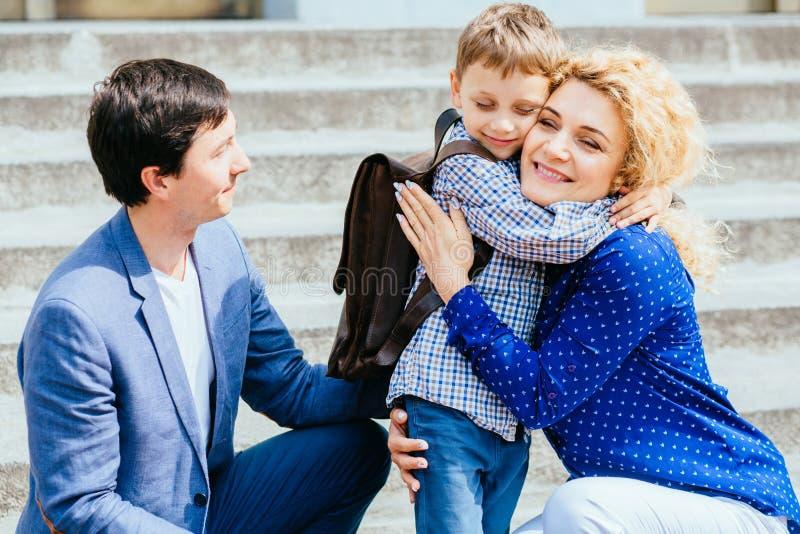 Godere del concetto 'nucleo familiare' Madre e papà che inviano la loro prima volta del ragazzo dell'allievo del bambino che stud immagini stock libere da diritti