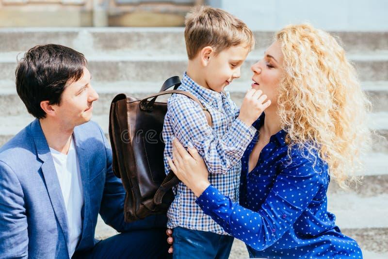 Godere del concetto 'nucleo familiare' Mamma felice e papà che inviano la loro prima volta del ragazzo dell'allievo del bambino c fotografie stock