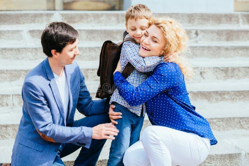 Godere del concetto 'nucleo familiare' Mamma felice e papà che inviano la loro prima volta del ragazzo dell'allievo del bambino c immagini stock libere da diritti