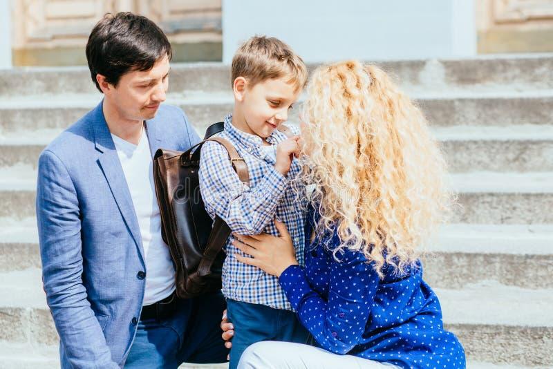 Godere del concetto 'nucleo familiare' Mamma felice e papà che inviano la loro prima volta del ragazzo dell'allievo del bambino c fotografia stock libera da diritti