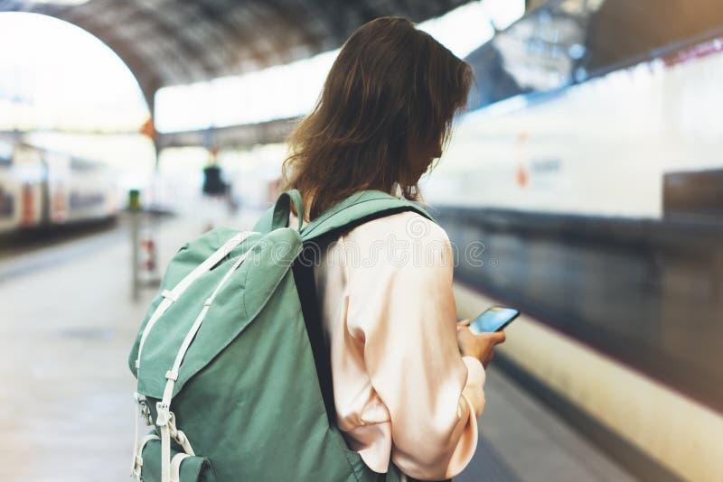 Godere del viaggio Giovane donna graziosa che aspetta sul binario della stazione con lo zaino sul treno elettrico del fondo facen fotografie stock libere da diritti