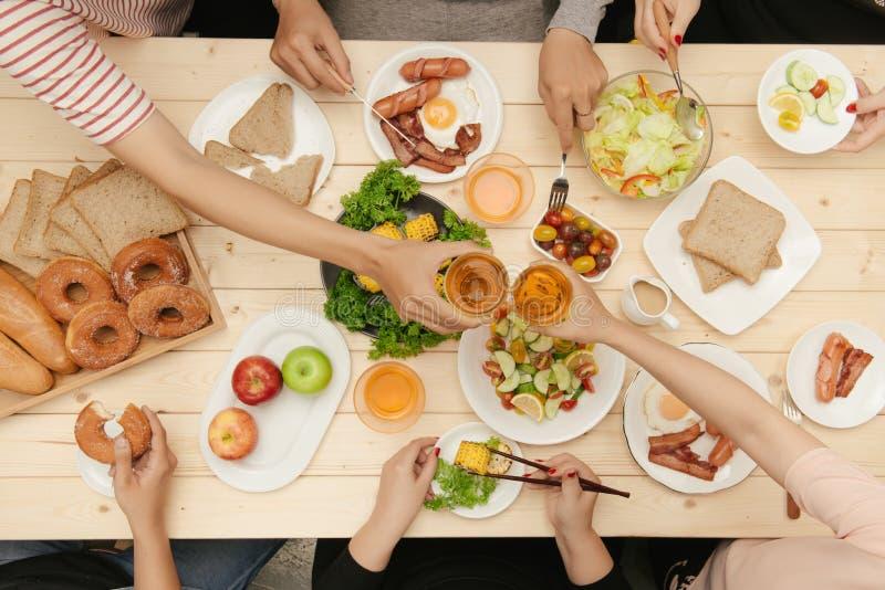Godere della cena con gli amici Punto di vista superiore del gruppo di persone cenando insieme mentre sedendosi alla tavola di le fotografia stock libera da diritti