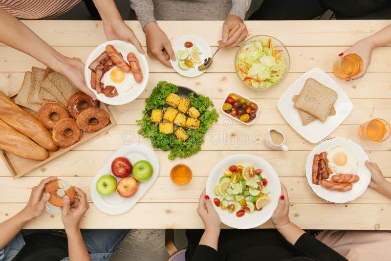 Godere della cena con gli amici Punto di vista superiore del gruppo di persone cenando insieme mentre sedendosi alla tavola di le immagine stock