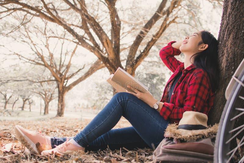 Godere della donna dei pantaloni a vita bassa di momento che legge un libro e che si siede sotto il grande albero sul parco fotografie stock