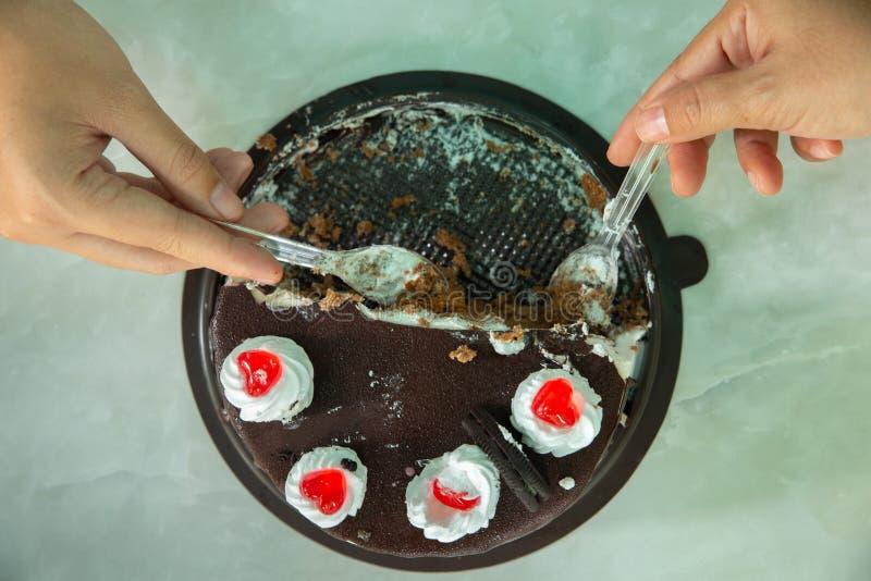 Godere delle mani della donna che mangiano il dolce di cioccolato fotografia stock libera da diritti
