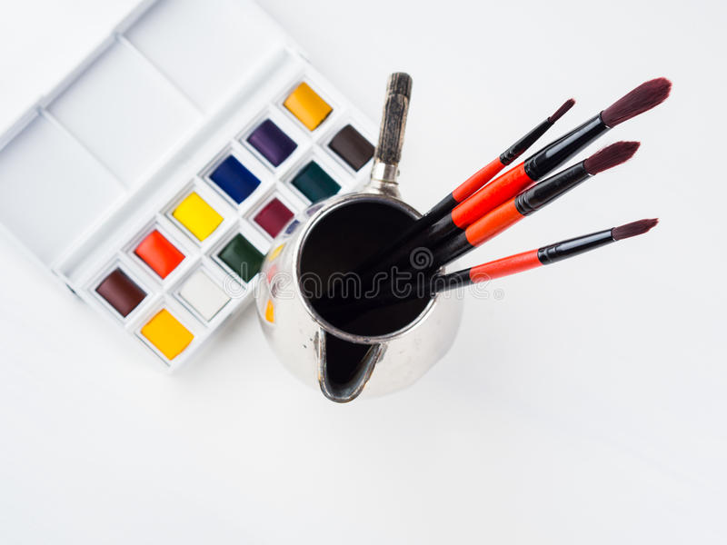 Godets et brosses d'aquarelle sur le blanc photo stock