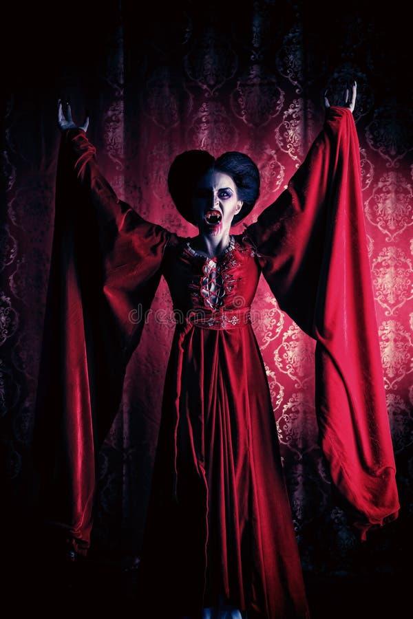 Godforsaken. Portrait of a bloodthirsty female vampire over red vintage background royalty free stock image
