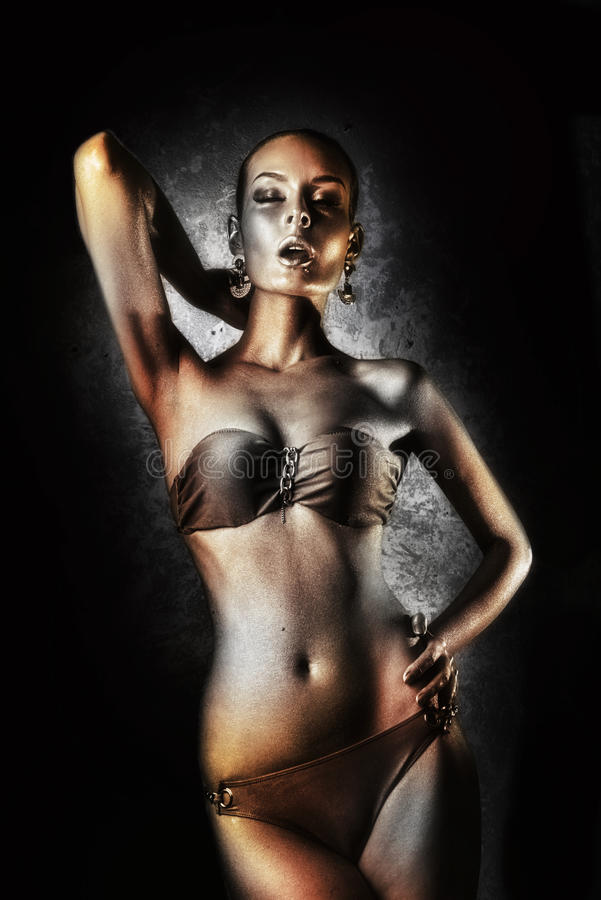godimento Donna lucida con body art dorato glamor Sui precedenti della parete grigia fotografia stock libera da diritti