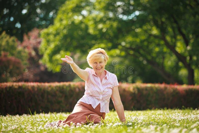 Godimento. Emozioni positive. Donna anziana uscente che riposa sull'erba fotografia stock