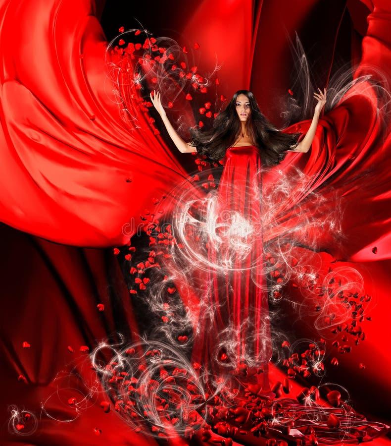 Godin van liefde in rode kleding met prachtige haar en harten stock foto