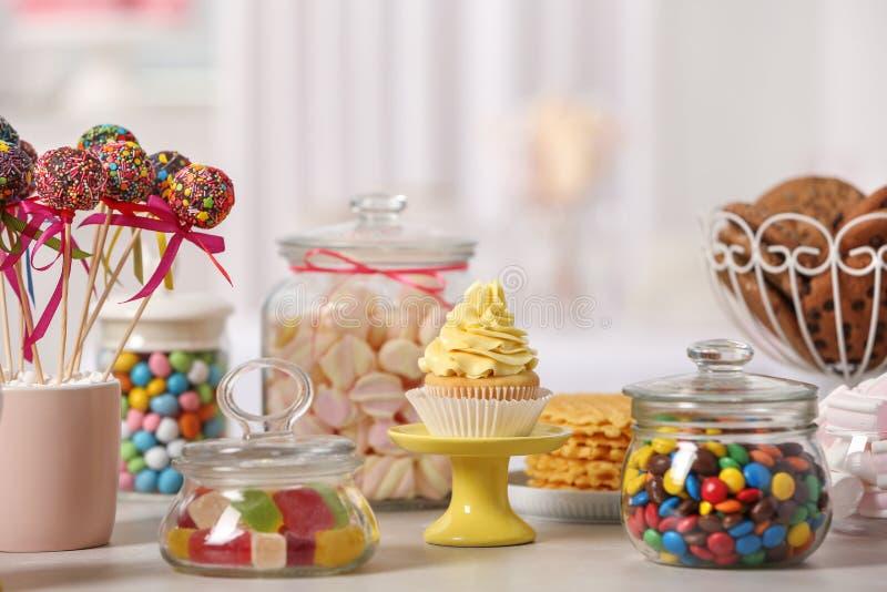 Godisstång med olika sötsaker på den vita tabellen arkivfoton