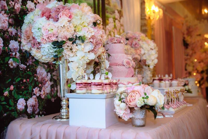 Godisstång och bröllopstårta Tabell med sötsaker, buffé med muffin, godisar, efterrätt arkivbild