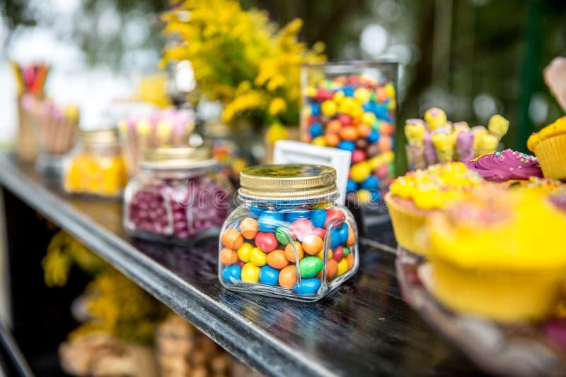 Godisstång och bröllopstårta Tabell med sötsaker, buffé med muffin, godisar, efterrätt arkivbilder