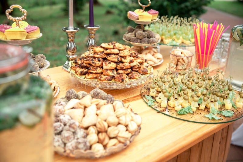 Godisstång och bröllopstårta Tabell med sötsaker, buffé med muffin, godisar, efterrätt royaltyfri bild
