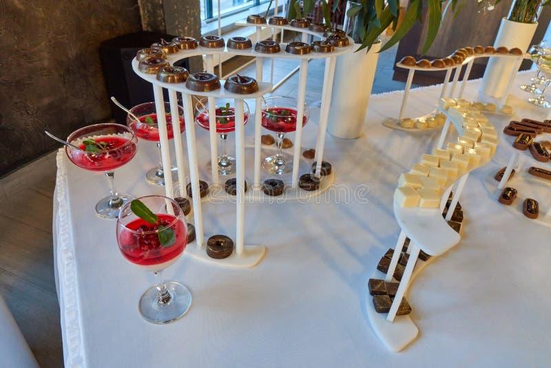 Godisstång på den vita tabellen med olika kunds av sötsaker och andra efterrätter arkivfoto