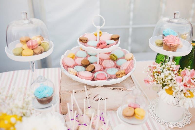 Godisstången med den keramiska vita plattan står med den färgrika smakliga makron-, rosa färg- och blåttmuffin på en buffétabell arkivfoton