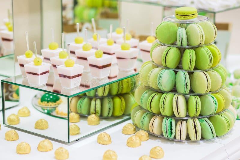 Godisstången med macarons, kakor, ostkakor, kaka poppar Färgrik grön makronpyramide royaltyfria bilder