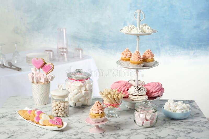 Godisstången med olika sötsaker på vit marmorerar tabellen arkivbilder