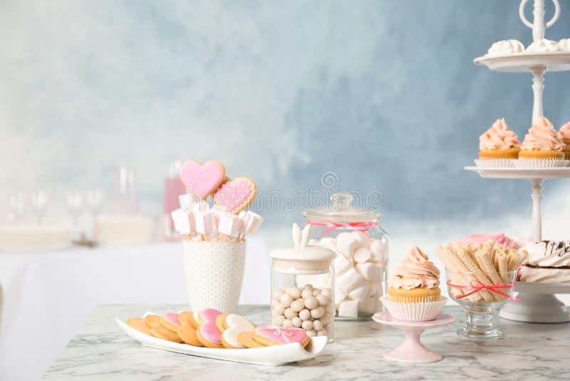 Godisstången med olika sötsaker på vit marmorerar tabellen royaltyfri bild