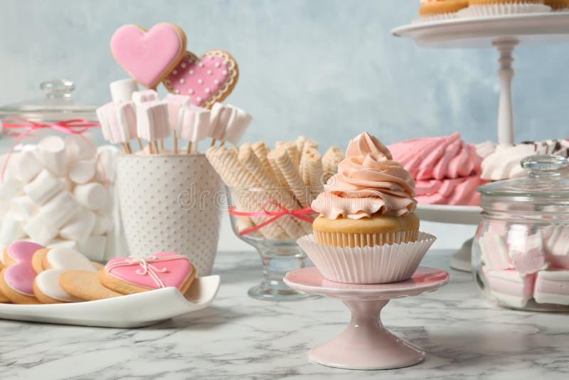 Godisstången med olika sötsaker på vit marmorerar tabellen arkivfoto